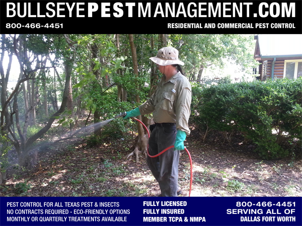 Bullseye Pest Managment Certified Applicator Steve Moseley treats a wooded area surrounding a log cabin for Carpenter Ants and other General Pest Control in Red Oak Texas.